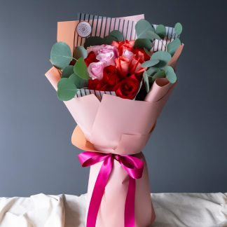 ช่อดอกกุหลาบสีแดง ชมพู และโอลด์โรส จัดเรียงสวยงามอย่างมีสไตล์