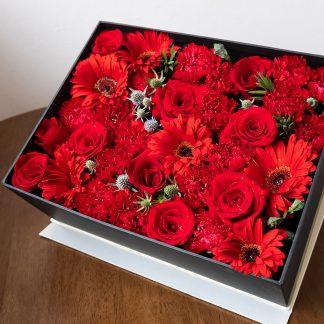 กล่องกุหลาบสีแดงสด และดอกเยอบีร่าสีแดง บรรจุภายในกล่องสีดำ ทำให้ดูหรูหรา
