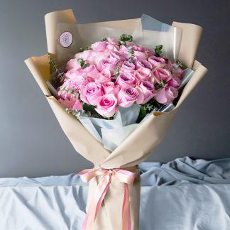 ดอกกุหลาบสีชมพู ห่อด้วยกระดาษสีครีมทรงเก๋ แซมด้วยใบยูคาลิปตัส