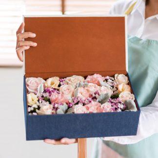 กล่องดอกไม้สีน้ำเงิน ที่เต็มไปด้วยดอกหลาบ ดอกไลเซนทัสสีชมพู