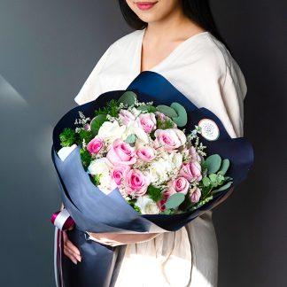 ช่อดอกกุหลาบสีชมพูและขาว จัดเป็นช่อทรงกลม ห่อด้วยกระดาษสีน้ำเงินกรมท่าตัดกัน